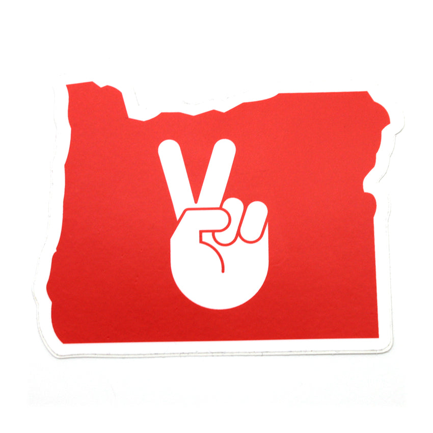 Red sticker in the shape of Oregon. In the center is a hand doing the peace sign.
