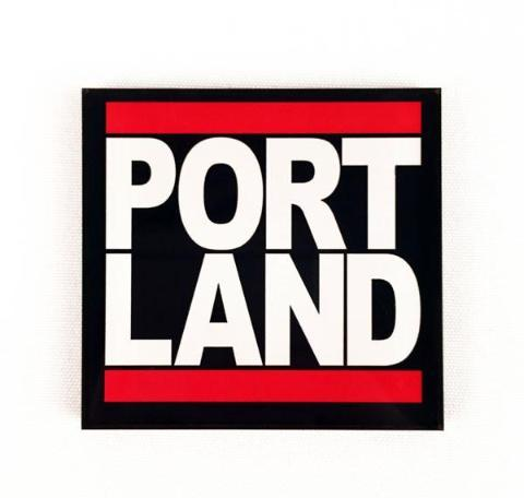 "Black square magnet with the ""Portland"" split and stacked on top of each other with red bars at the top and bottom, in the style of Run DMC's famous logo."