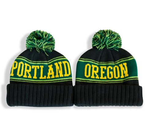 Green and yellow Pom knitted beanie with center stripe Reading Portland Oregon across in Varsity style font. Large Pom on top.