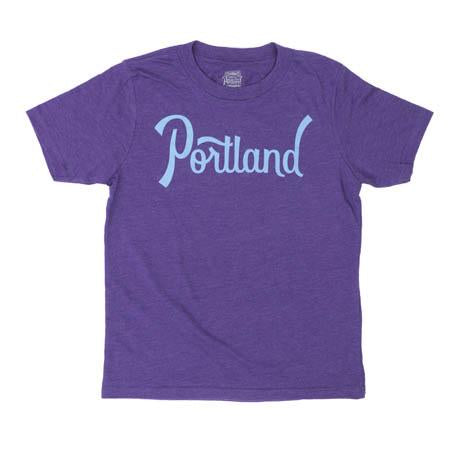 Kid's purple T-shirt with Portland written across chest in our signature font in blue.