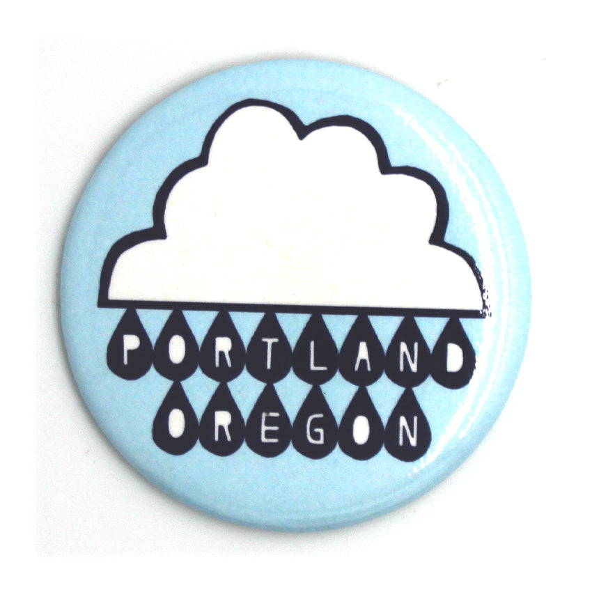 Light blue circle magnet with a rain cloud and in the rain drops it reads Portland Oregon.