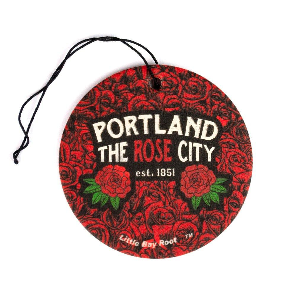 "Circle air freshener that reads ""Portland The Rose City est. 1851"" with the entire background being a field of roses."