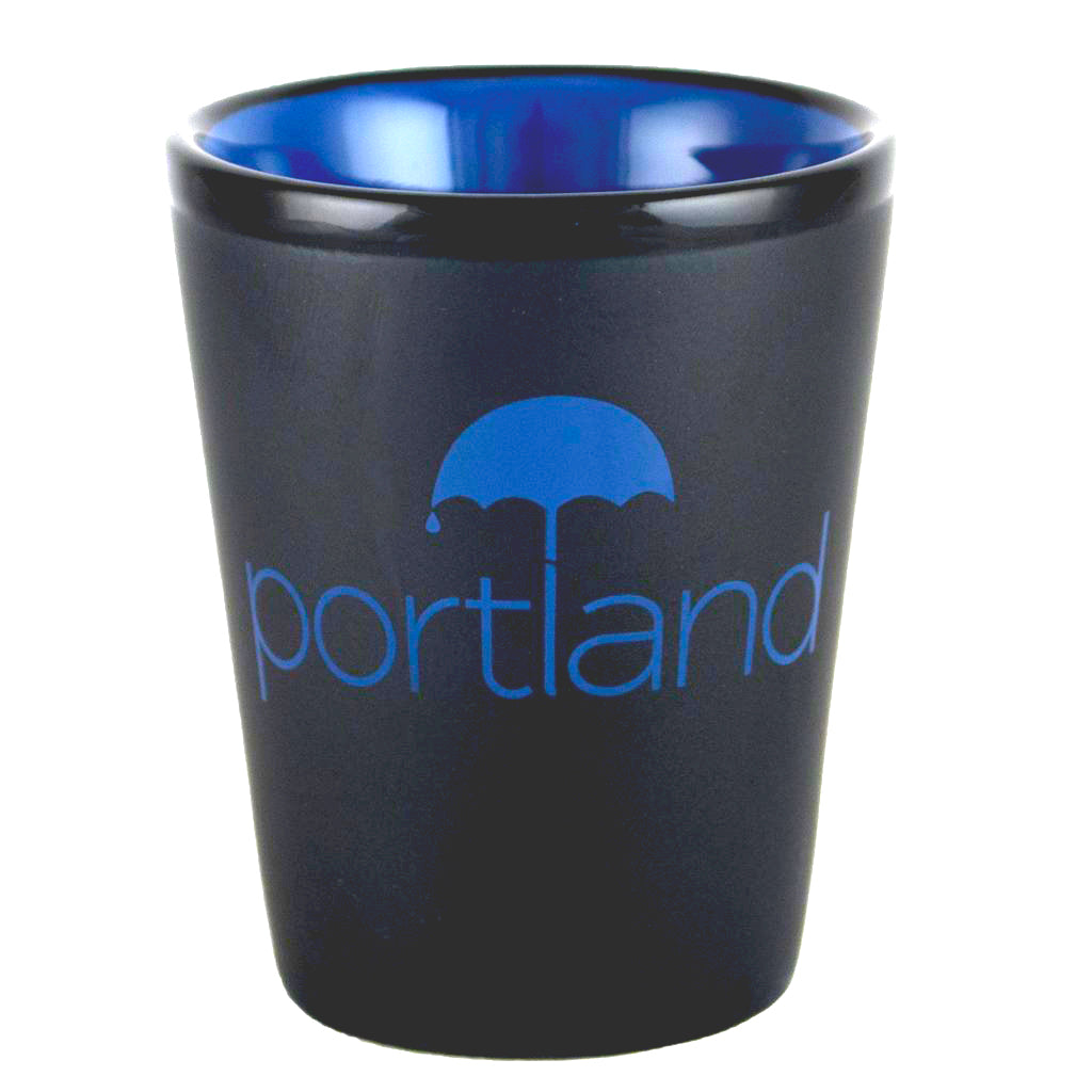 Matte black and blue shot glass featuring the word Portland on the side with an umbrella over it and a raindrop coming off the umbrella.