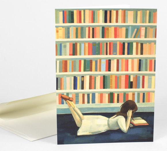 Greeting card depicting a girl laying on the floor reading a book with a shelf of books behind her.