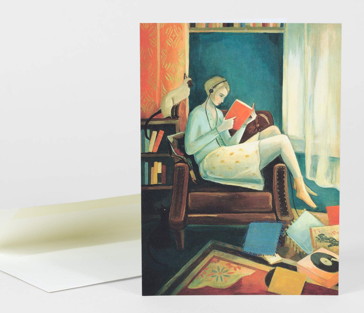 An illustrative greeting card depicting a woman with headphones on in a chair reading a book. There is a cat on the bookshelf behind her and pillows as well as a record player on the ground in front of her.
