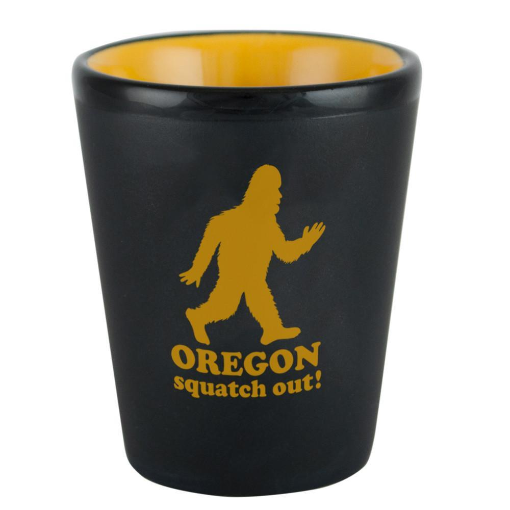 "Matte black and yellow shot glass with ""Oregon Squatch Out!"" written on the side of it, complete with a profile of Sasquatch above the letters."