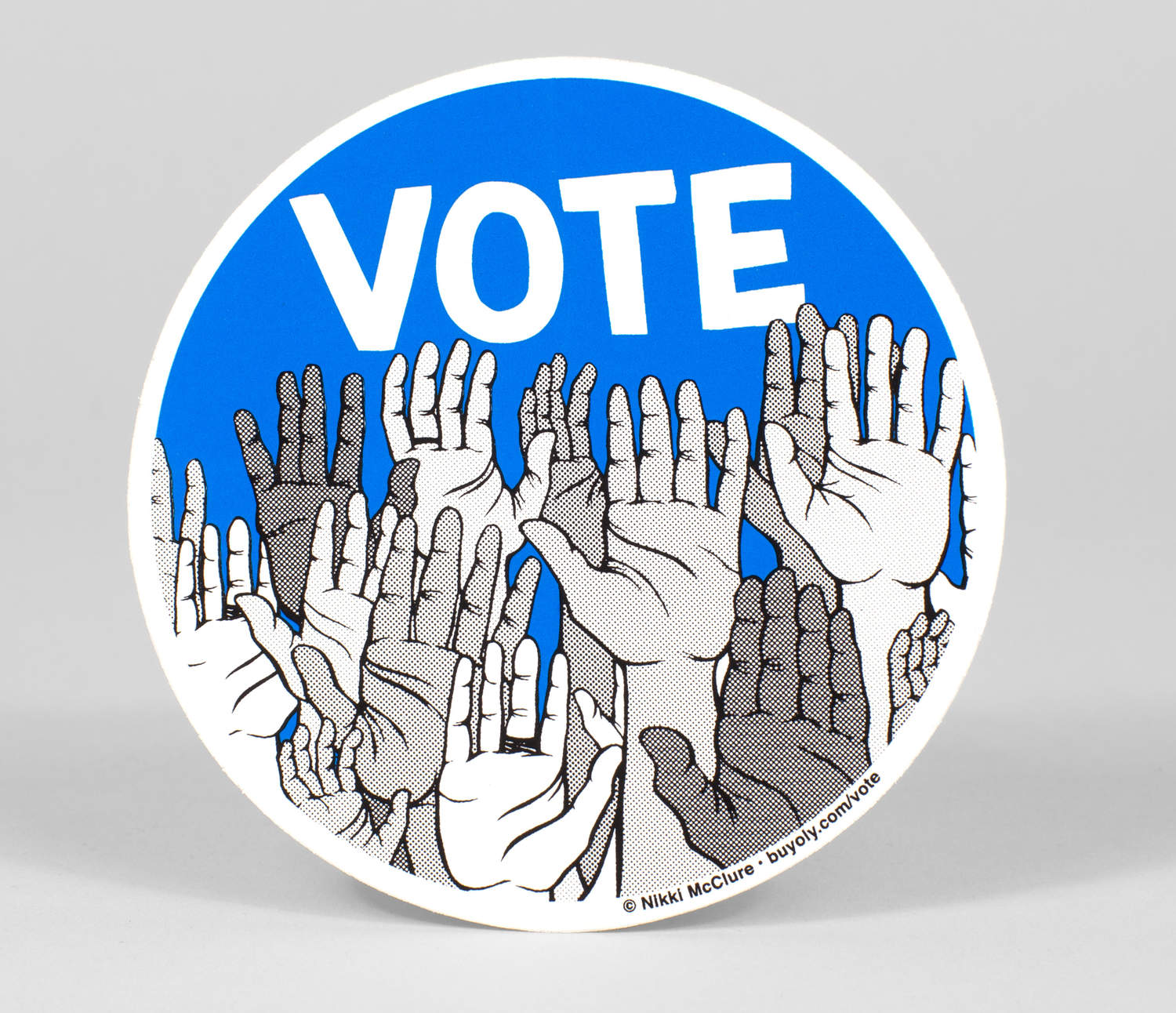 Blue circle sticker that says Vote on the top with a bunch of raised hands below it.