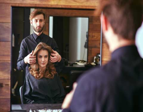 hairdresser doing a haircut to client