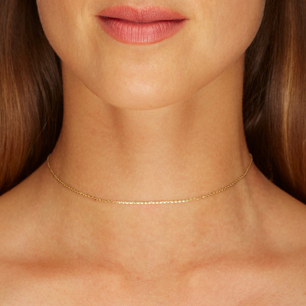 This fine 14 karat gold necklace is the ultimate statement of minimalism. It is the perfect gold necklace for women who love to layer jewels.   Our Basic Fine Necklace is available in two lengths. A gold choker necklace in 34 cm extendable to 37cm and a gold necklace in 39cm extendable to 42cm.