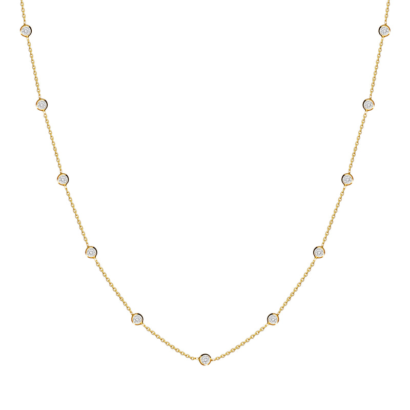 This delicate 14 karat gold necklace is handmade and features sparkling bezel - set stones. Diamond gold necklace.