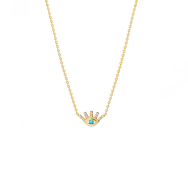 This 14 karat gold necklace with diamonds featuring a protection eye is our dream jewelry piece. The pendant features pave set diamonds on the lashes and a hand set turquoise stone in the center of the eye.