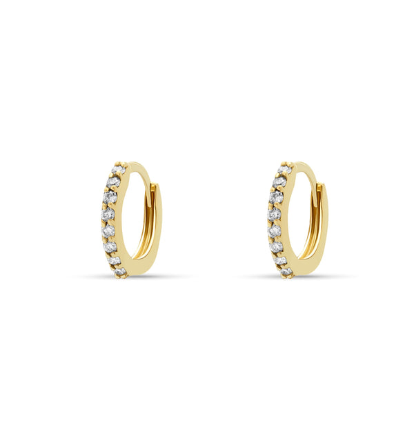 Our 14 karat gold huggie earrings feature handset diamond pave stones and are the ultimate essential for an every day sophisticated look.