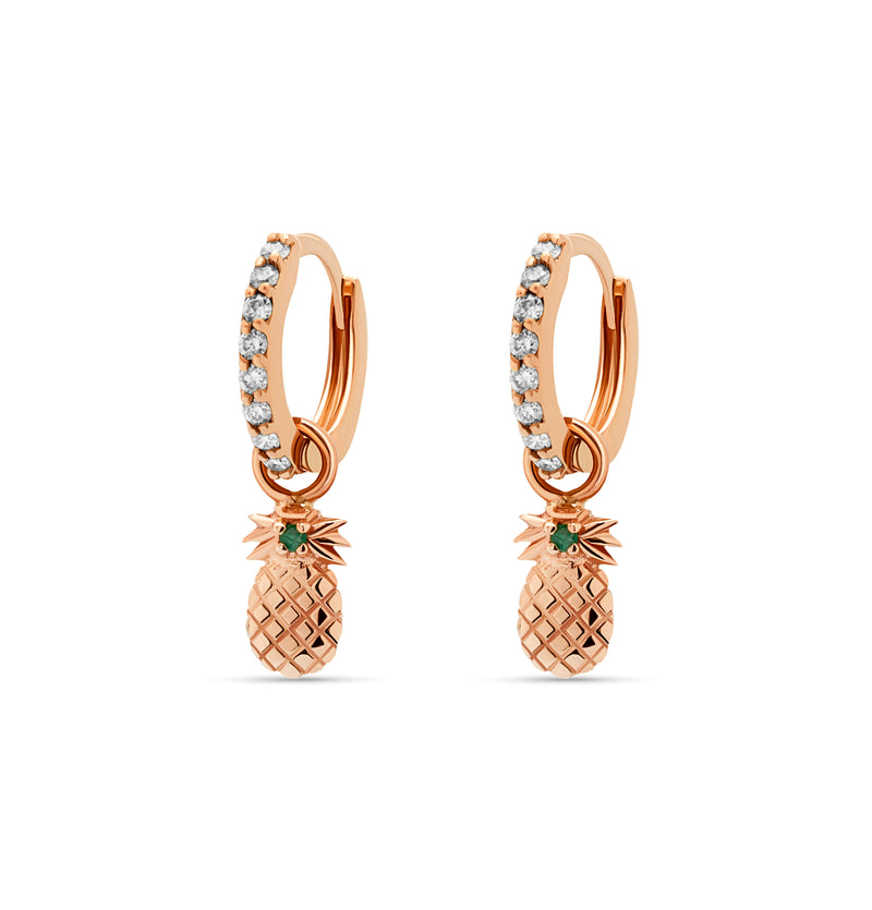 Our diamond gold huggie earrings in 14 karat gold feature pineapple charms with a handset green sapphire stone. A beautiful diamond earring that feels light and comfortable on the ear.  rosegold earring.