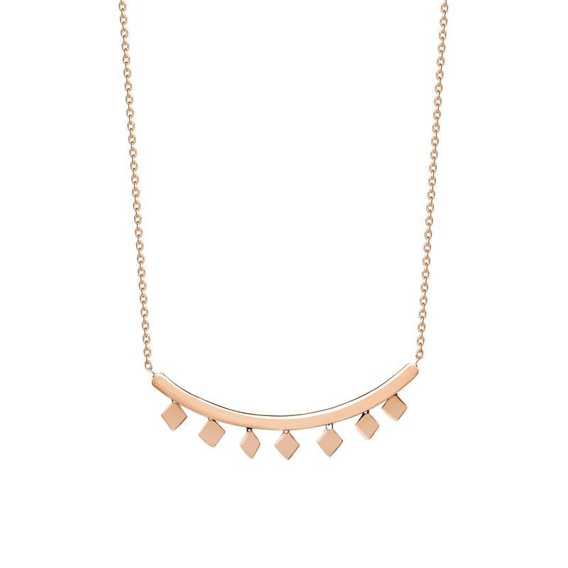 The Etnia Necklace in 14K gold features a bar with dangling rhomb charms. We love to layer this necklace with our Tribal Charm Necklace for an even more expressive look.