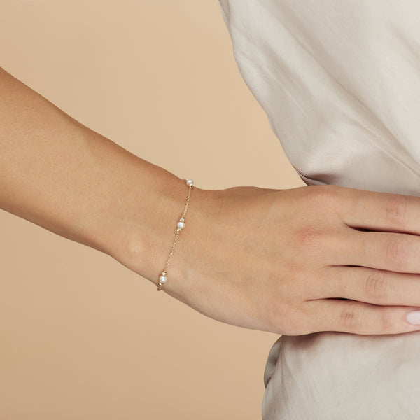 This handmade 14 karat gold pearl bracelet is an essential classic for every day. Each freshwater pearl is encased by diamond cut gold balls that reflect the light and add an extra sparkle to your wrist.