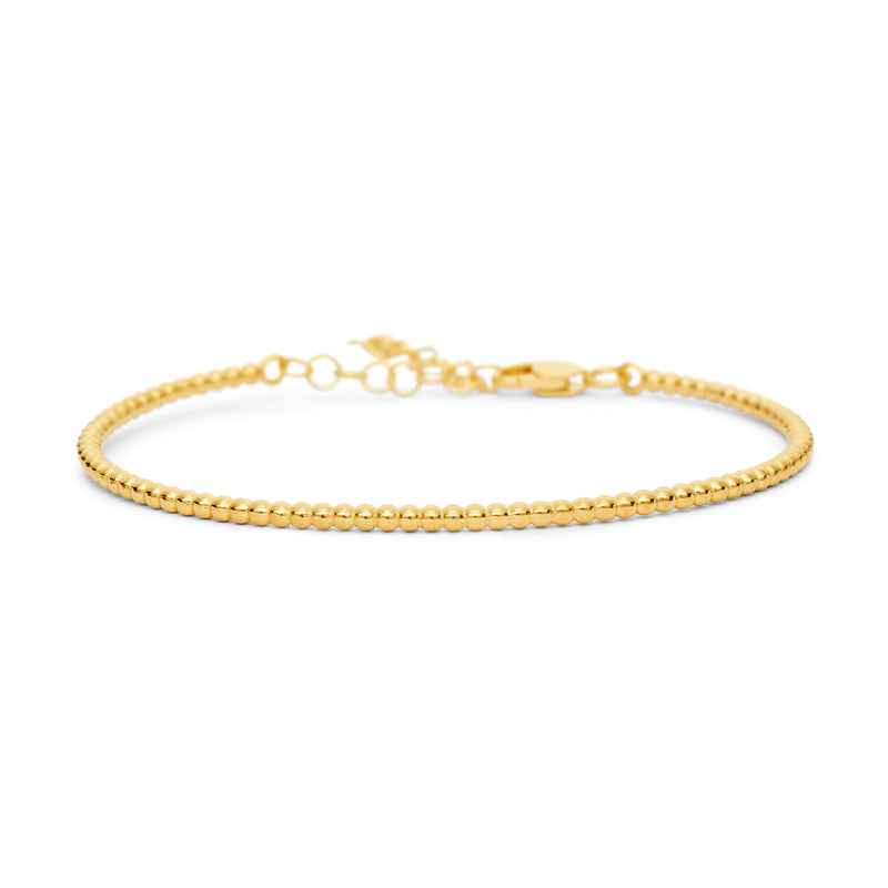 A delicate, yet solid Bangle Bracelet made of lined up gold balls. It is an essential bangle bracelet that is perfect for every day wear. Its chain and lock on the back side make this bracelet super comfortable and safe to wear.