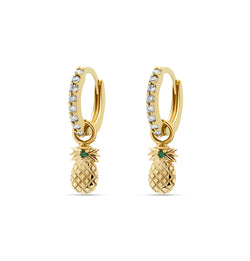 Our diamond gold huggie earrings in 14 karat gold feature pineapple charms with a handset green sapphire stone. A beautiful diamond earring that feels light and comfortable on the ear.