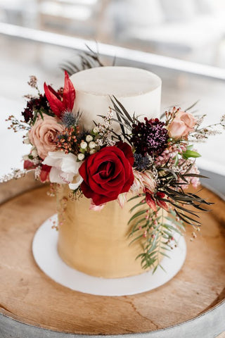 Wedding cake flowers on a semi nude gold cake featuring red luxe roses in Geelong Melbourne