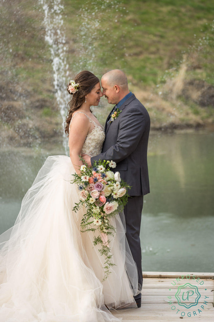 bride and groom posing in front of a lake, holding beautiful bouquet of flowers