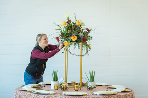 florist adding wedding flowers to table centerpiece for western wedding