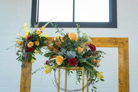 western wedding arch red and yellow flowers gold accents