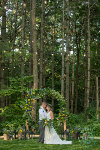 bride and groom with floral wreath backdrop and woodland area in the background