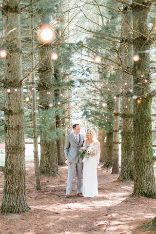 bride and groom in woods with lights