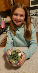 young girl potting succulents