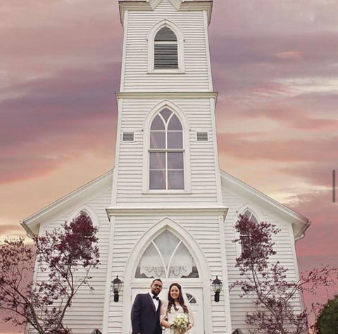 bride and groom standing outside church with sunset