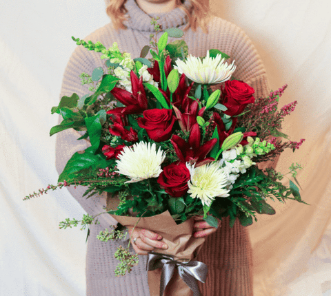 full bouquet of red and white flowers with greenery