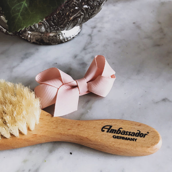 Wood baby brush made containing boar bristles and packaged in zero waste cardboard.