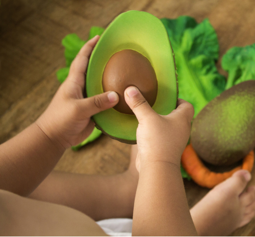 Arnold the Avocado Natural Rubber Toy with child.