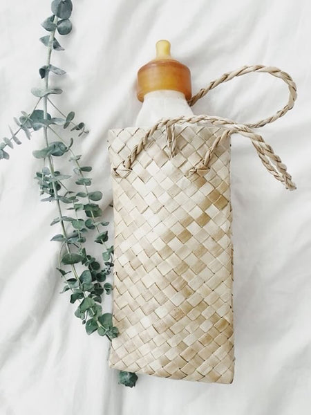 Baby Quoddle plastic-free glass baby bottle 300ml size inside leaf bag.