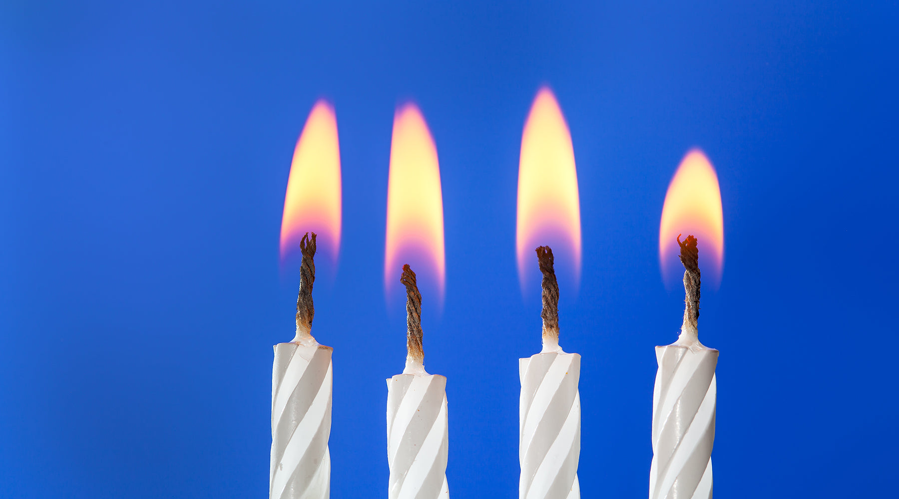 Four white cake candles burning in a row | Nikki Darling Australia