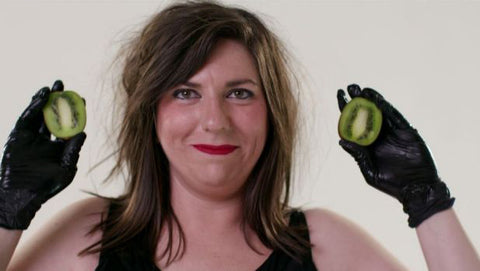 Maeve Marsden holding up kiwi fruits with latex gloves - still taken from Lady Sings It Better and Claude Educational Video | Nikki Darling Australia