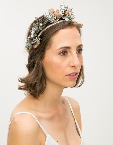 Model wears headband embellished with fabric flowers
