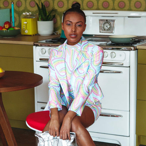 Seated model wearing pastel rainbow biker jacket over a matching high neck printed pastel mini dress