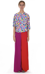 Model wearing wide leg red and purple pants and a mosaic printed top