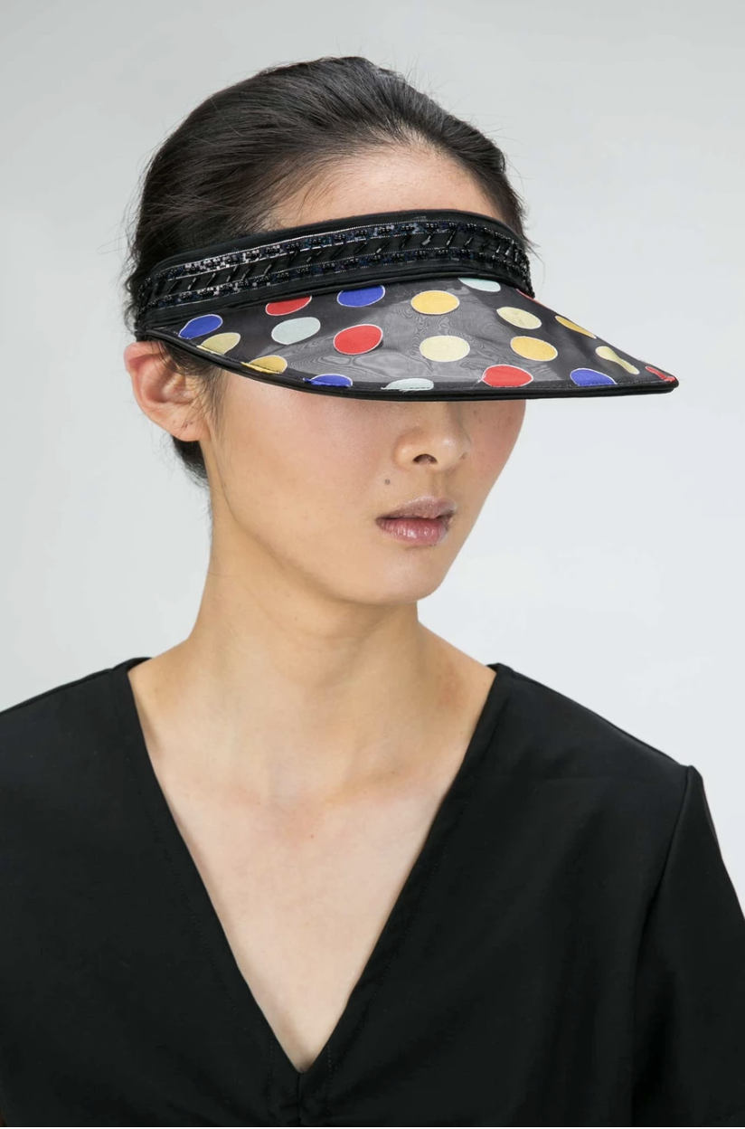 Model wears organza visor with embroidered spots