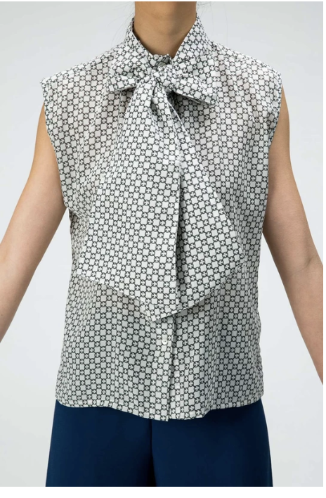 A close up of a woman wearing a sleeveless printed blouse with a oversized bow neckline