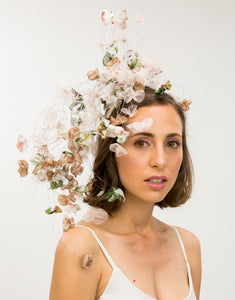 Woman wearing fascinator with pastel silk petals on silver wire cascading to shoulder