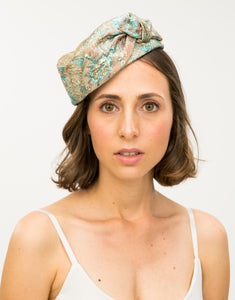 Model wears Jacquard pillbox hat with knot detail