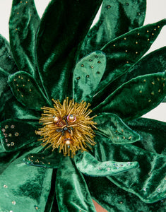 Close up of an emerald green velvet flower fascinator with yellow bead detailing in centre of flower