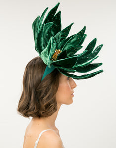 Side profile of woman wearing an oversized velvet emerald green flower fascinator with Swarovski pearls, crystals and Japanese glass beads