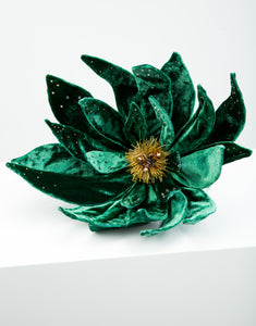 An emerald green velvet flower fascinator with yellow bead detailing in centre of flower