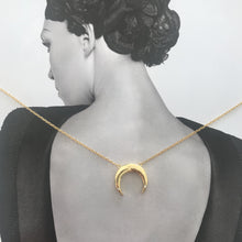 Load image into Gallery viewer, Gold necklace with moon pendant with white sapphire gems details laid on magazine photo