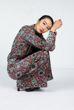 Load image into Gallery viewer, Model curled over wearing a wide leg pant with Moroccan tile print and matching blouse