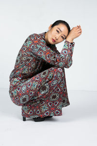 Model curled over wearing a wide leg pant with Moroccan tile print and matching blouse