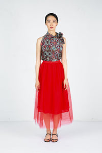 Model stands in sleeveless printed top with red tulle skirt