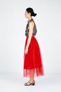 Side view of model wearing red tulle skirt with printed sleeveless blouse